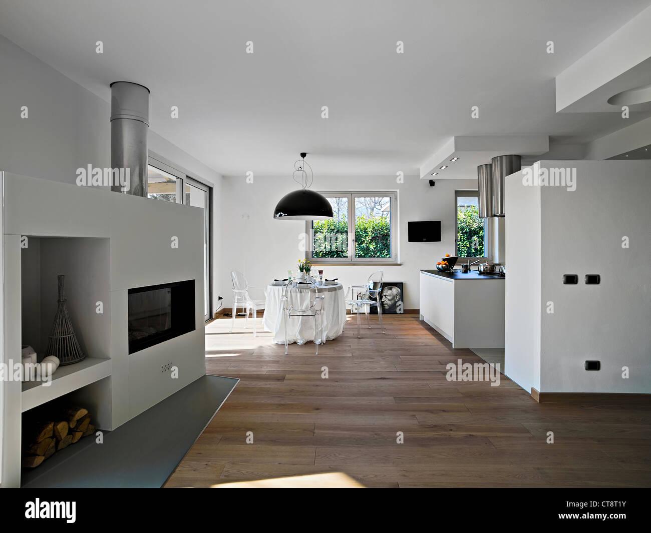 Salle à manger moderne avec cheminée et vue sur la cuisine Photo Stock