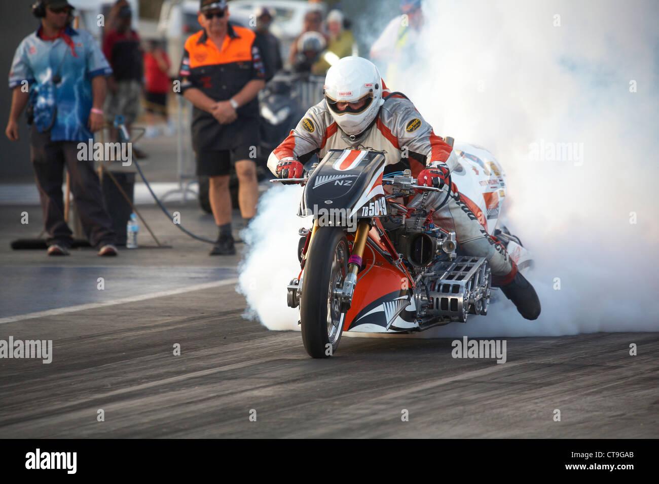 Nouvelle-zélande drag racer moto, Athol WIlliams, effectue un burnout roulant à chauffer le pneu arrière Photo Stock