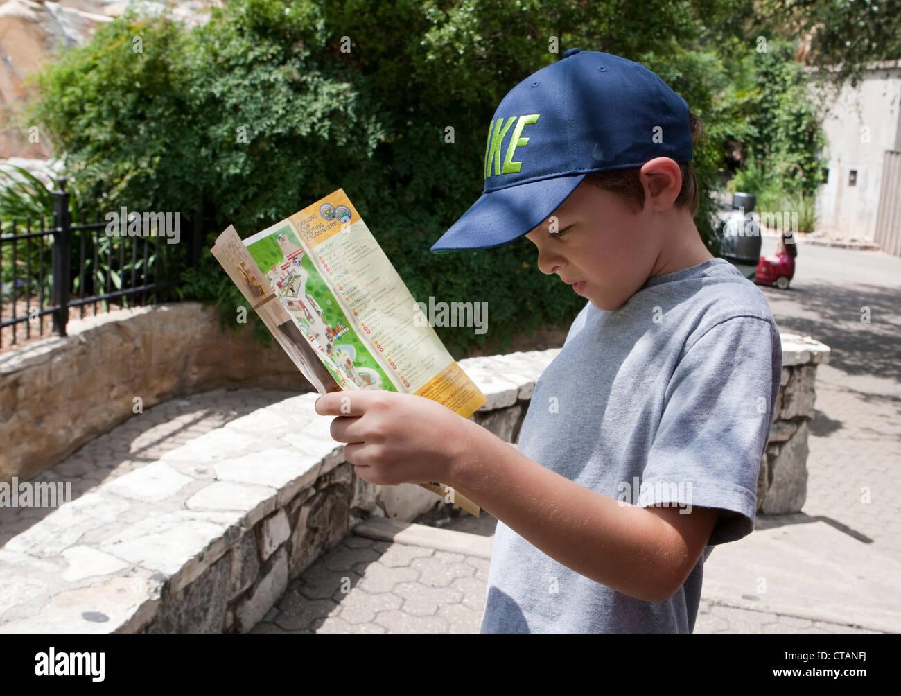 7 ans garçon mexico-lit dépliant et regarde la carte de San Antonio Zoo au Texas. Photo Stock