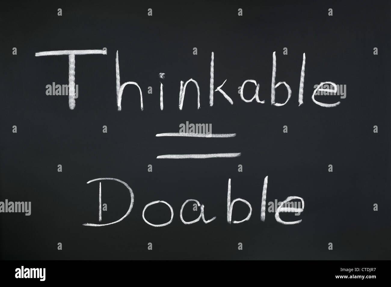"""Les mots 'pensable = faisable"""" écrit sur un tableau noir. Un regard sur la pensée positive. Photo Stock"""