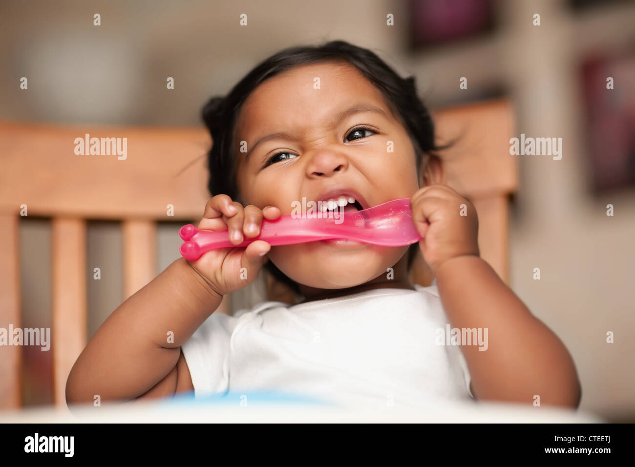 Bébé affamé de mettre une cuillère à sa bouche et il mordant Photo Stock