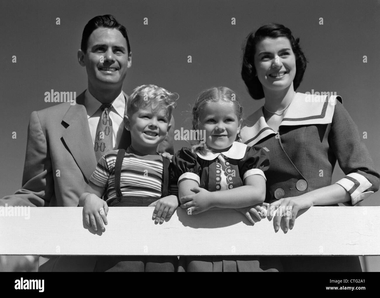 1950 PORTRAIT SMILING FAMILY Père Mère Fils Fille debout derrière une clôture blanche Photo Stock