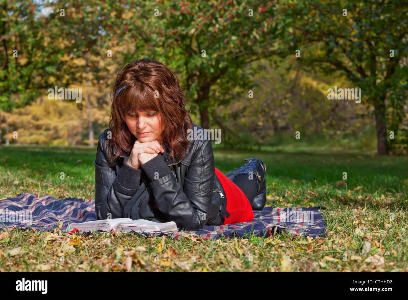 Une jeune femme lisant une Bible Et méditant dans un parc; Edmonton, Alberta, Canada Banque D'Images