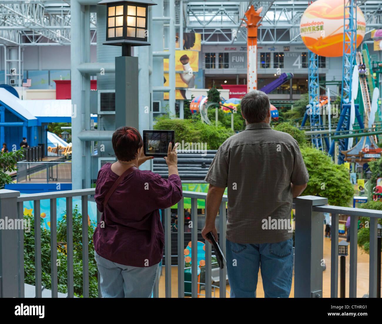 Une femme à l'aide d'un ordinateur tablette de prendre une photographie, Mall of America, Minneapolis, Photo Stock