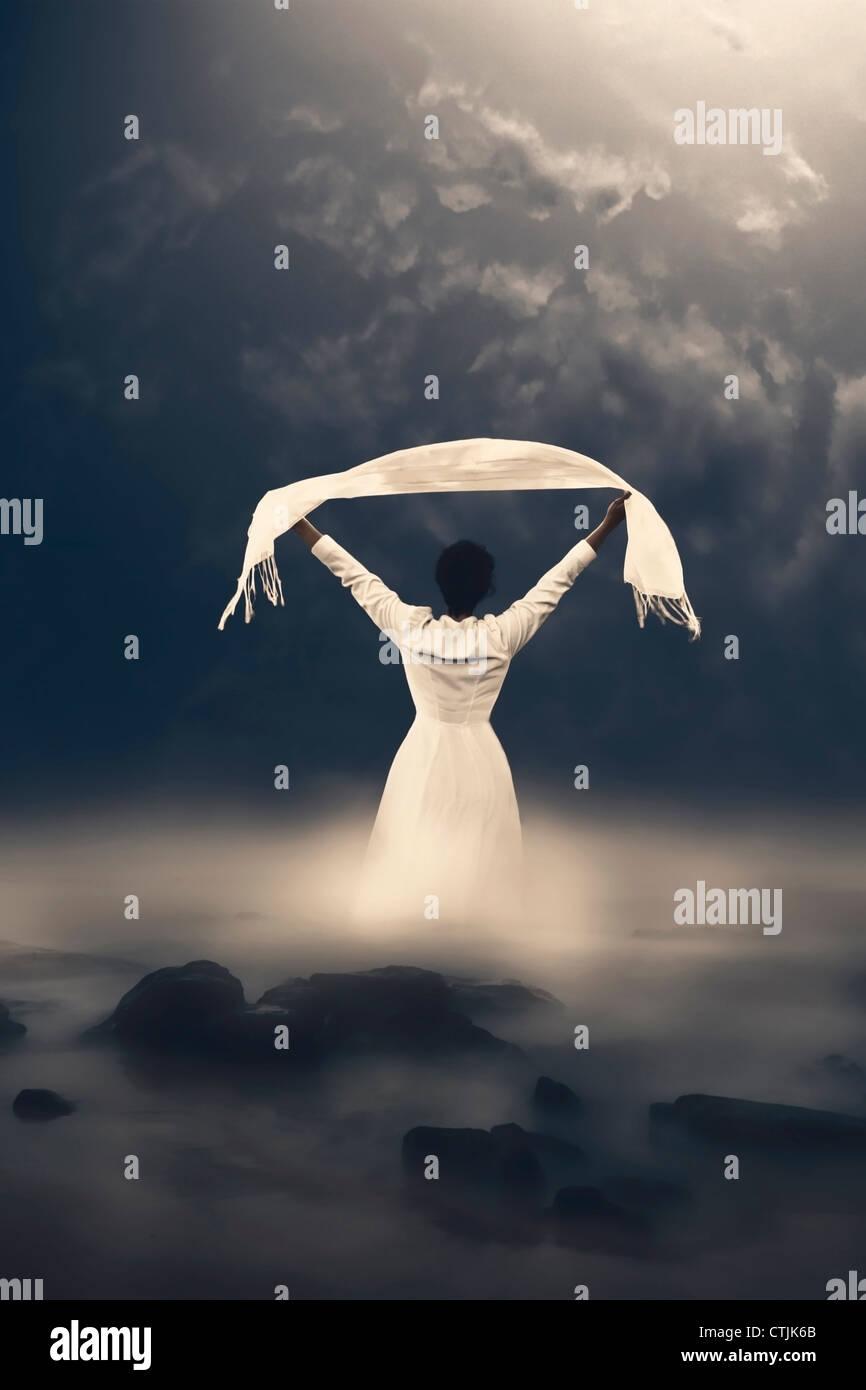 Une femme en robe blanche sort de l'eau brumeuse Photo Stock