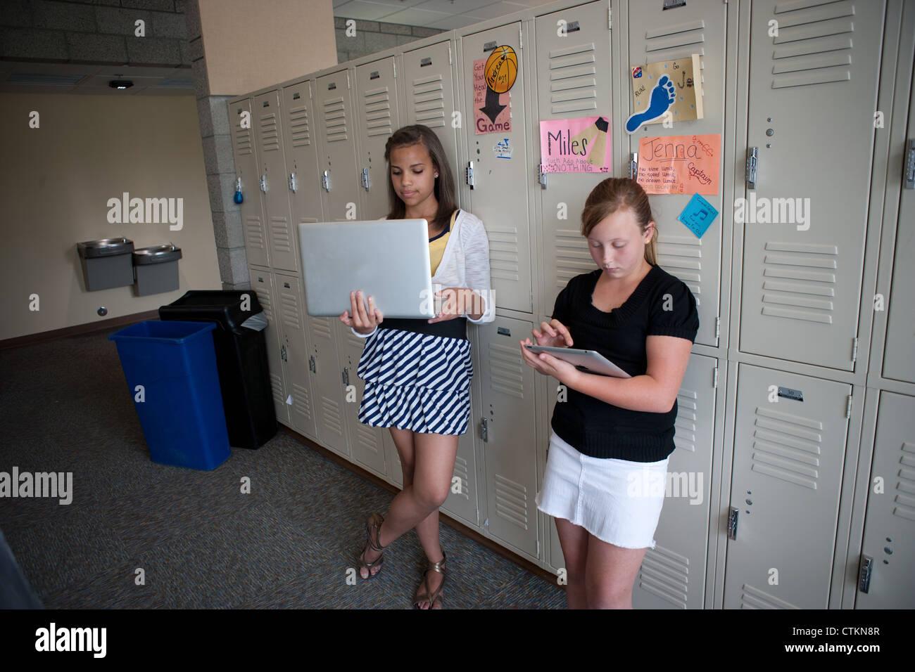 Les jeunes filles à l'aide d'ipad et d'un ordinateur portatif dans le couloir de l'école intermédiaire. Banque D'Images