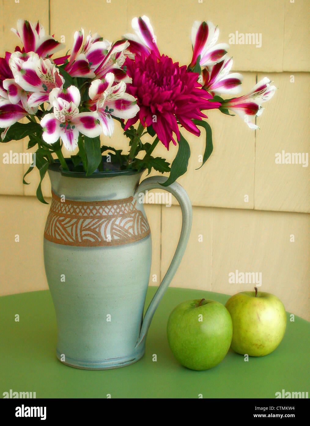Fleurs rouges et blanches (azalée) dans un vase sur une table à côté de la pomme verte, New York USA Banque D'Images