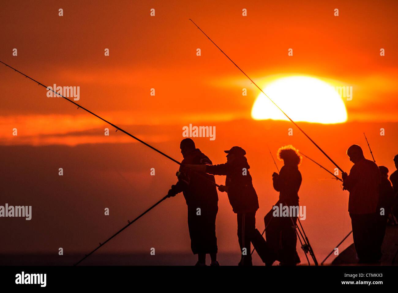 Silhouettes d'hommes pêcher avec des cannes et des lignes au coucher du soleil à Aberystwyth, Ceredigion Photo Stock