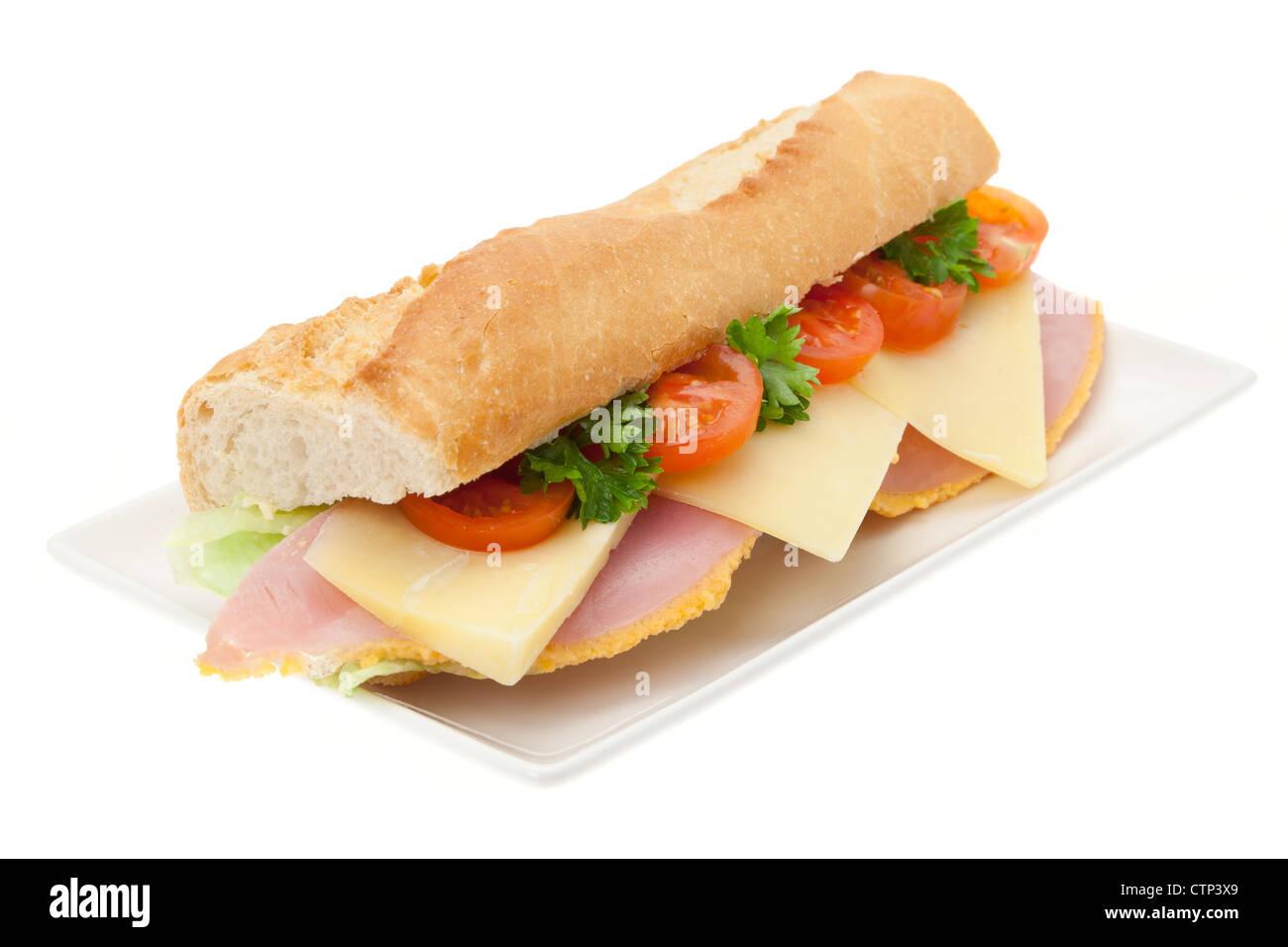 Un jambon frais, fromage et salade sandwich dans une baguette française sur une plaque blanche chine - studio Photo Stock