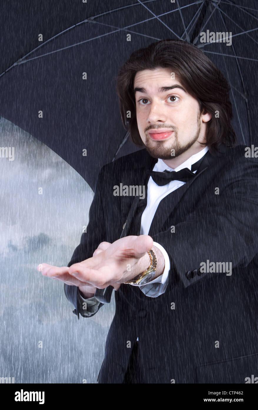 Parapluie Homme avec vérification de la pluie (ou de compensation) optimiste à venir Photo Stock