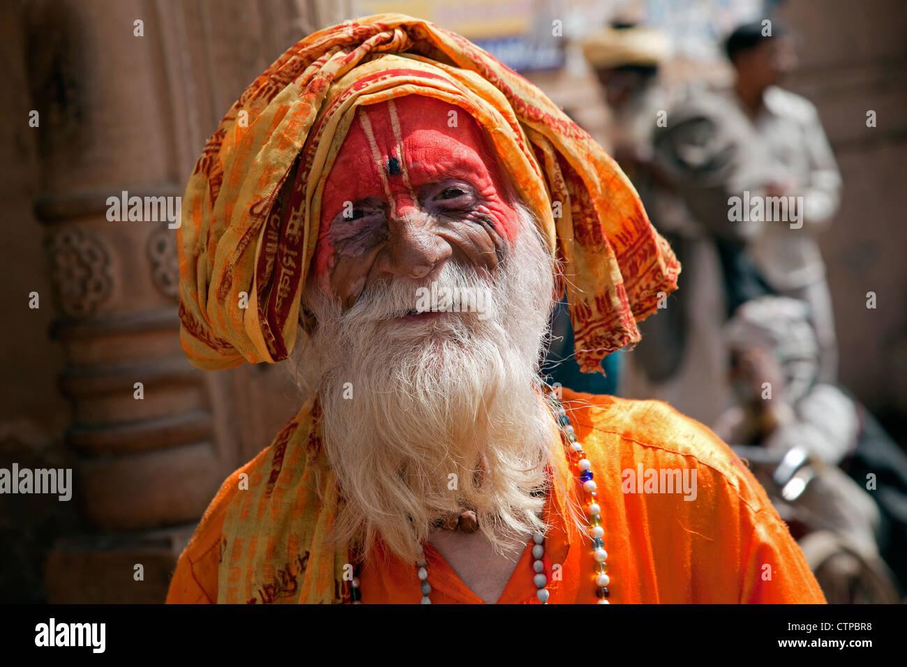 Portrait de l'ancien disciple de Hare Krishna avec barbe grise habillé en robe orange en face de temple en Inde, Govardhan Banque D'Images