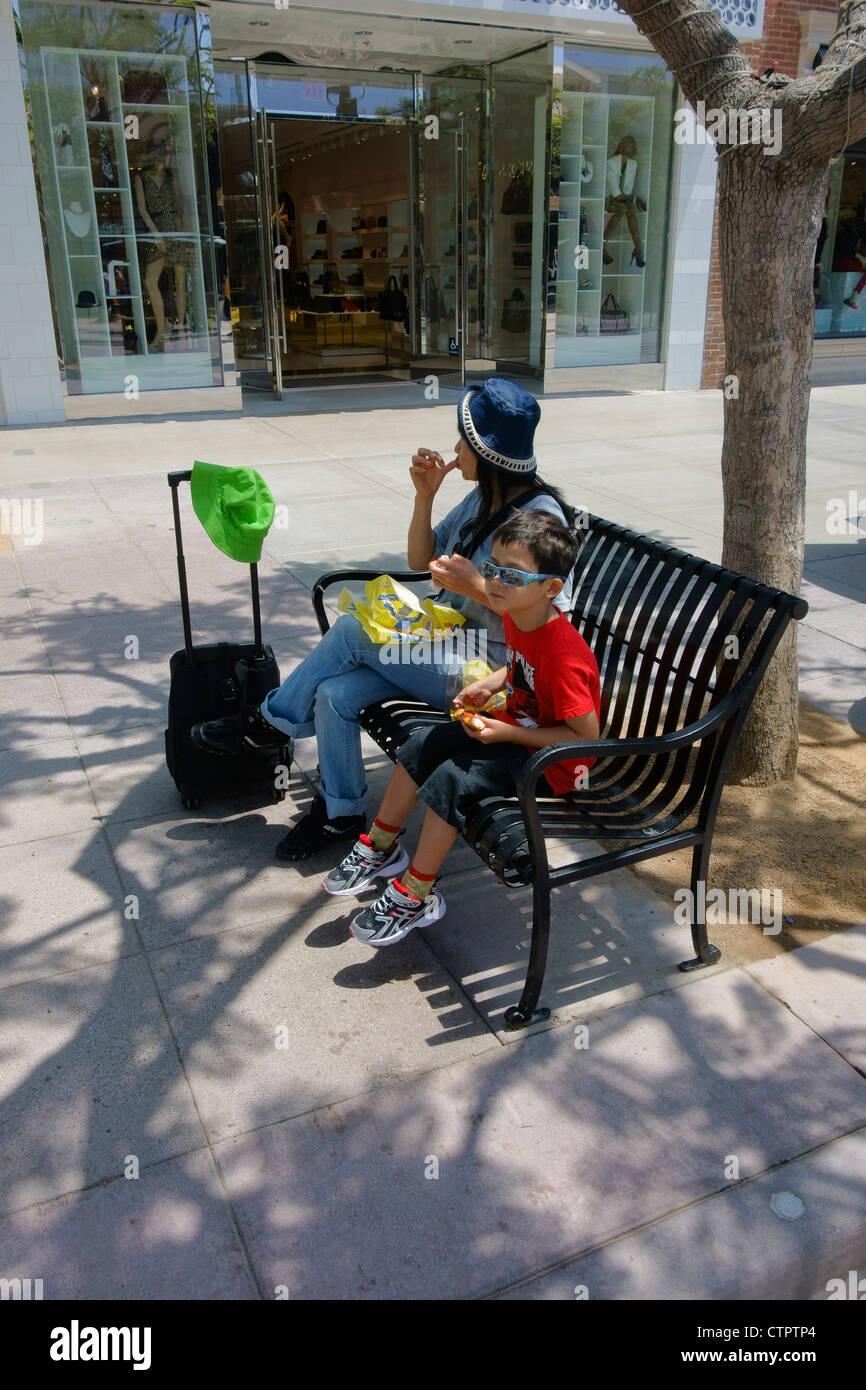 Une mère et son jeune fils manger des collations sur un banc public à Santa Monica, en Californie. Banque D'Images