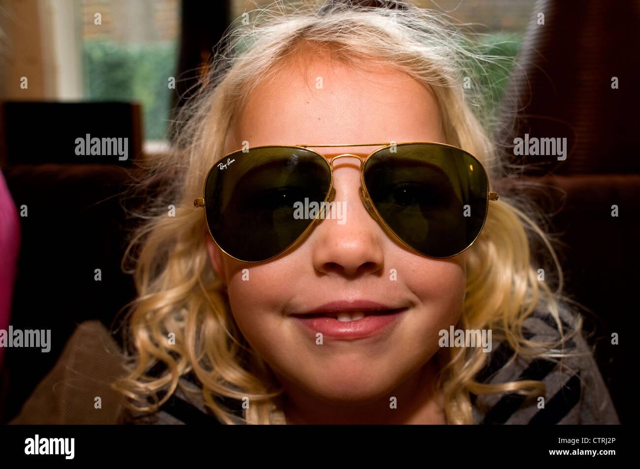 27a4bf752daec1 Petite fille posant avec une paire de lunettes de soleil Ray Ban ...