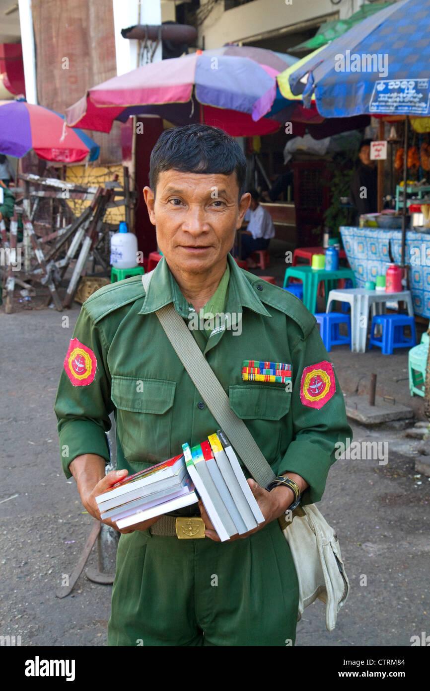 Ancien combattant en uniforme militaire birman vente de livres dans la rue à Yangon (Rangoon), la Birmanie (Myanmar). Banque D'Images