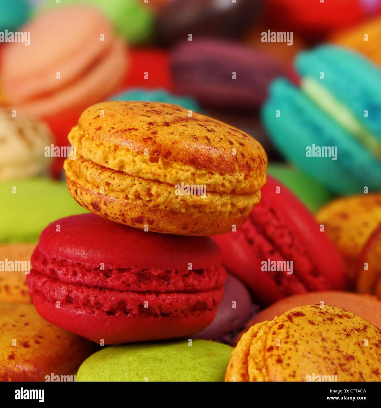 Macarons pamplemousse et cerise sur un assortiment de macarons colorés Photo Stock