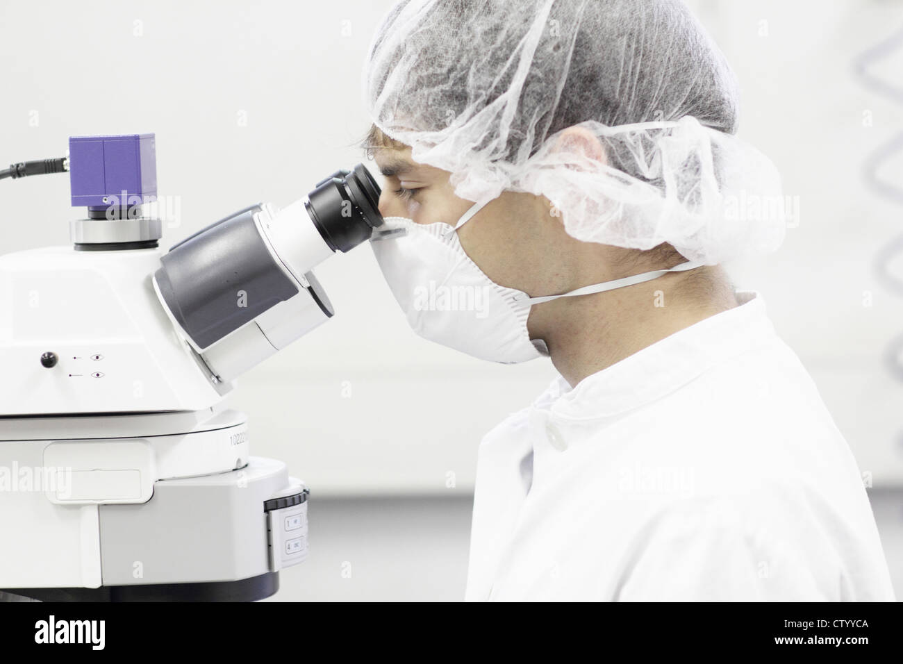Scientist using microscope in lab Photo Stock