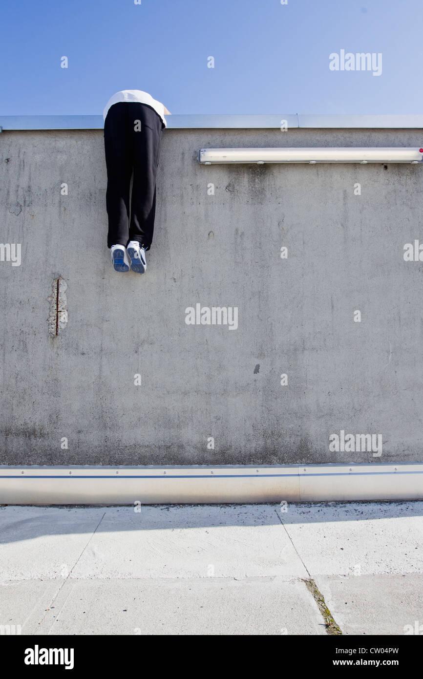 L'échelle de l'homme mur on city street Photo Stock