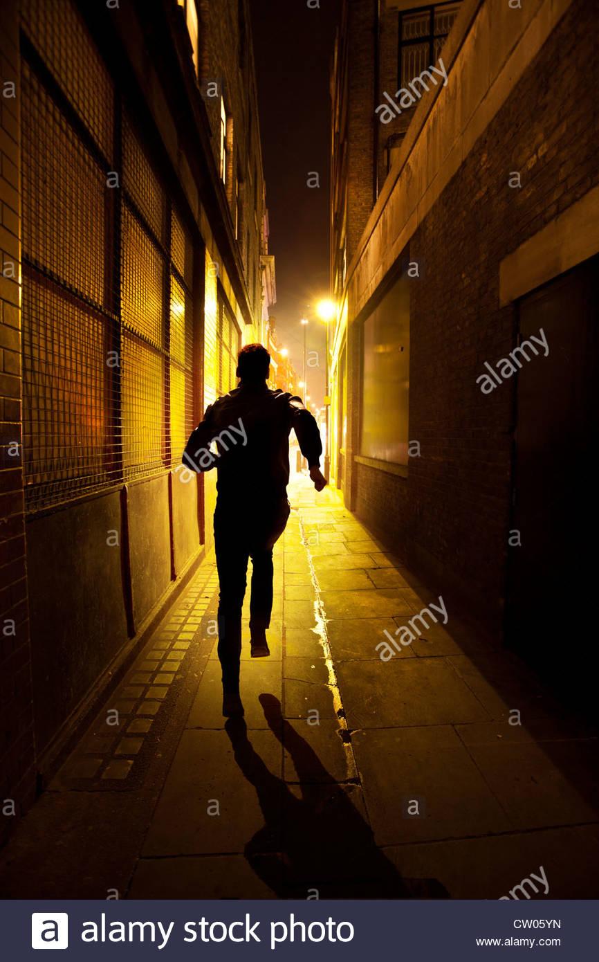 Homme qui court vers le bas une ruelle de nuit Photo Stock
