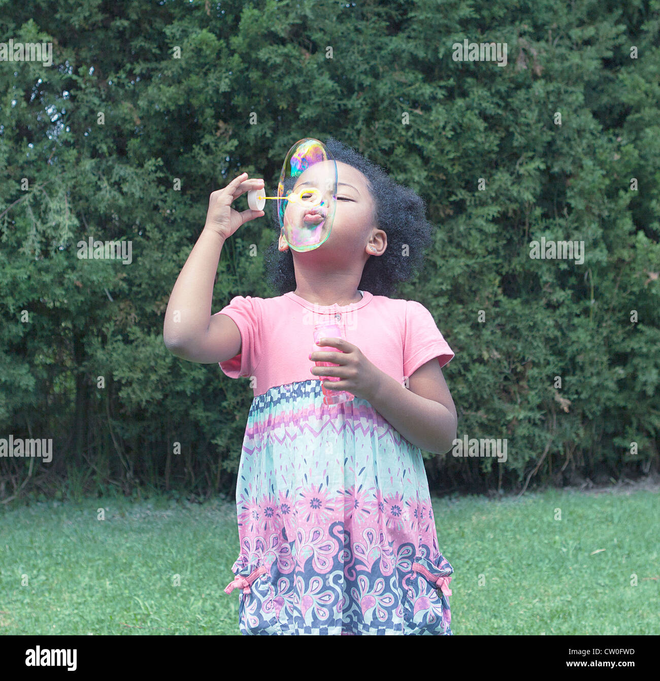 Girl blowing bubbles outdoors Photo Stock