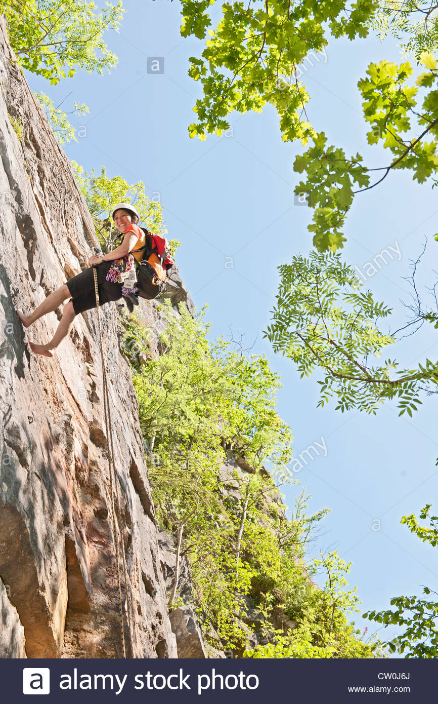 Climber scaling steep rock face Photo Stock