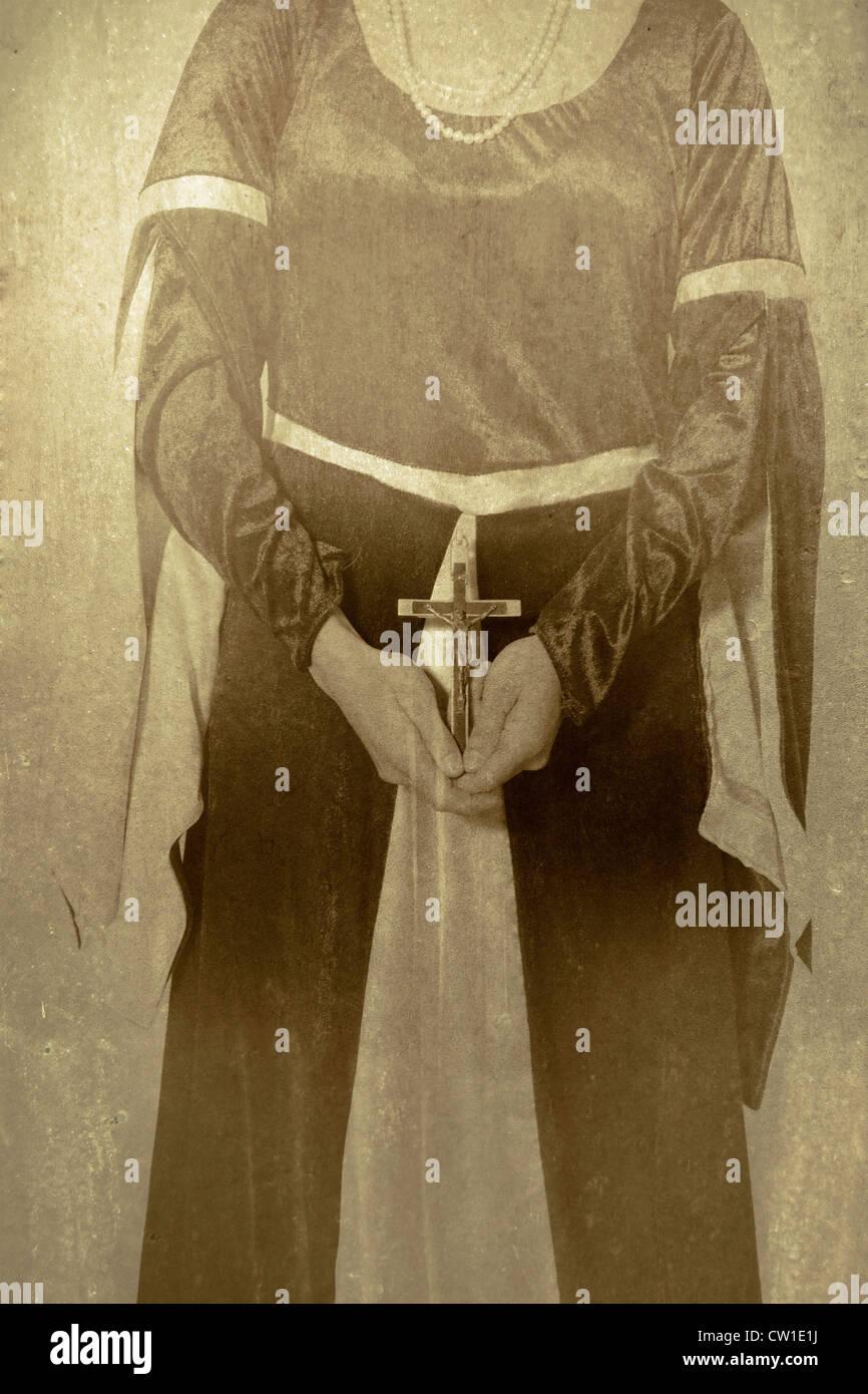 Une femme en robe victorienne tenant un Crucifix dans ses mains Banque D'Images
