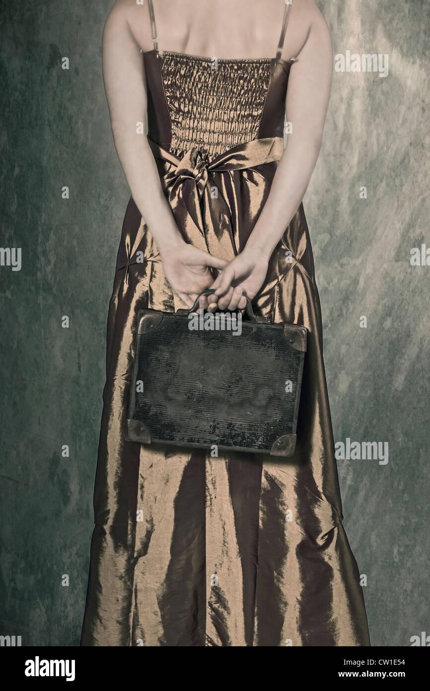 Une femme dans une période tenant une petite robe, vieille valise derrière son dos Photo Stock