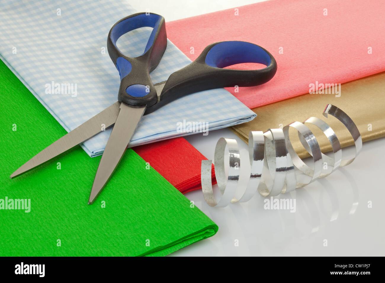 Ciseaux, papier d'emballage et ruban sur une table Photo Stock