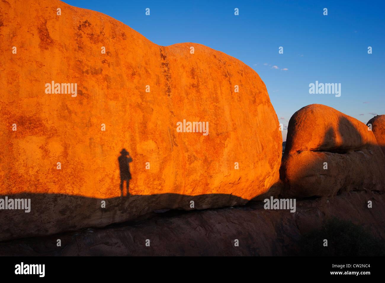 Ombre d'un homme contre l'Spizkoppe rock formation.Désert du Namib en Namibie. Photo Stock