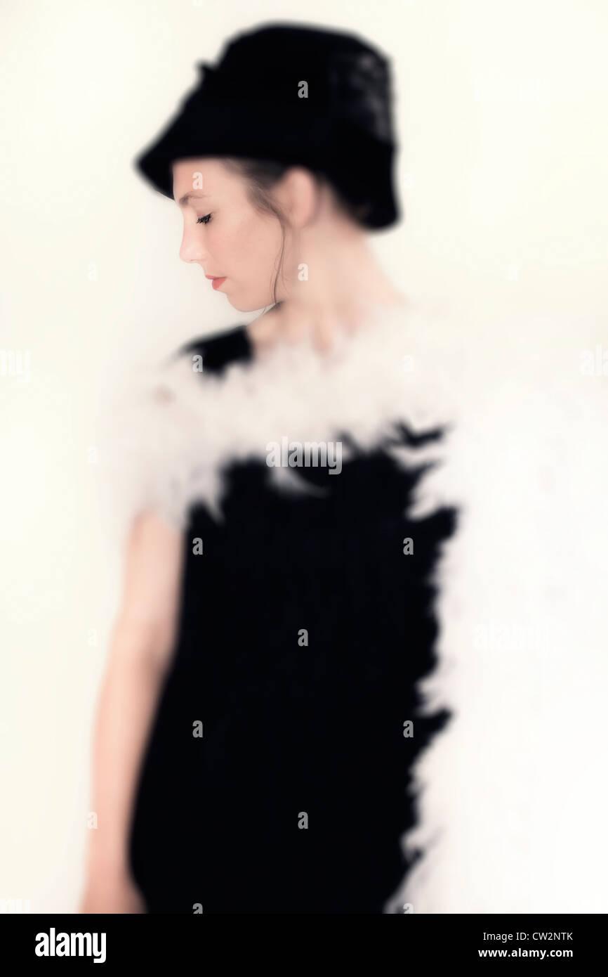 Une jeune femme dans une élégante robe noire avec chapeau et plume boa Banque D'Images