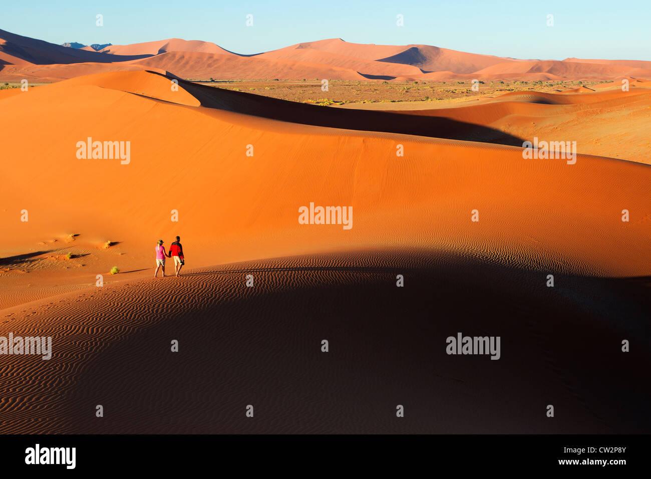 Couple en train de marcher le long du bord des dunes de sable, Soussvlei,la Namibie. Photo Stock