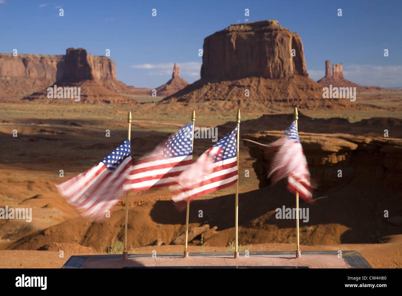 Drapeaux américains blowing in wind devant red buttes flèches colorées Monument Valley Navajo Tribal Park Le sud Banque D'Images