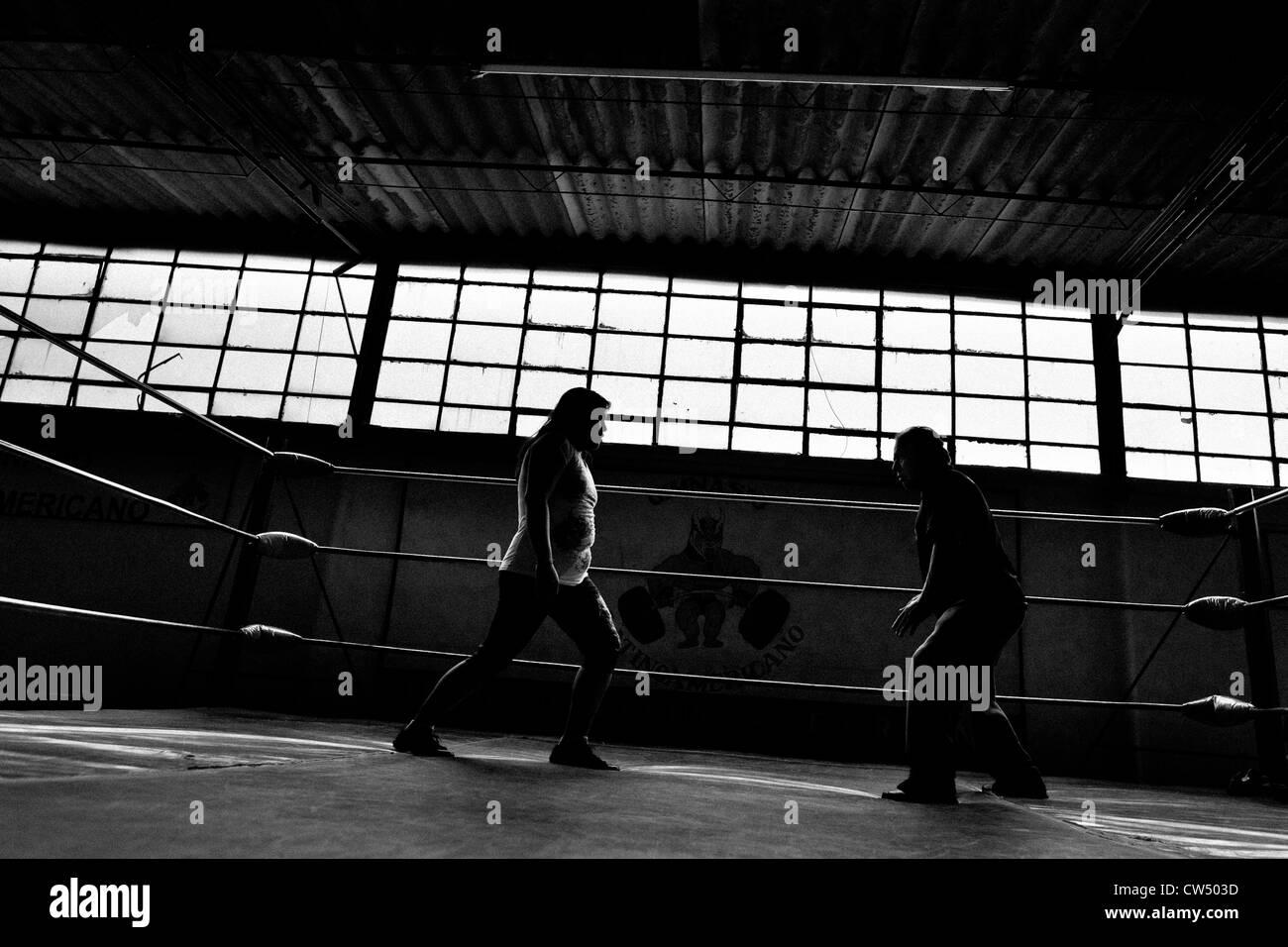 Un lutteur de lucha libre féminin s'entraîne avec son entraîneur dans un Gym Sports de combat Photo Stock
