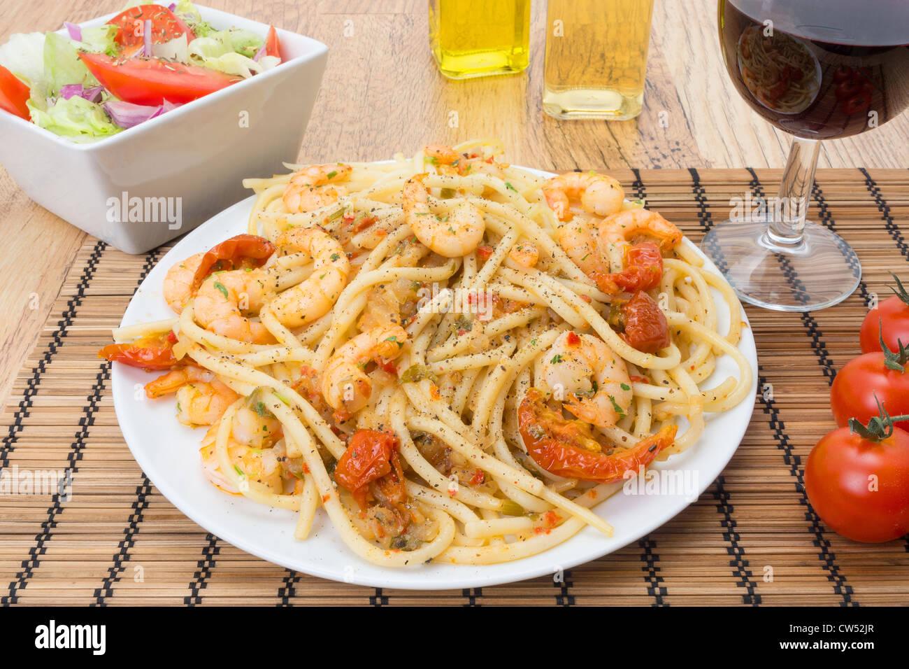 Grosses crevettes jetés par les pâtes bucatini et garni de tomates séchées au soleil - studio Photo Stock