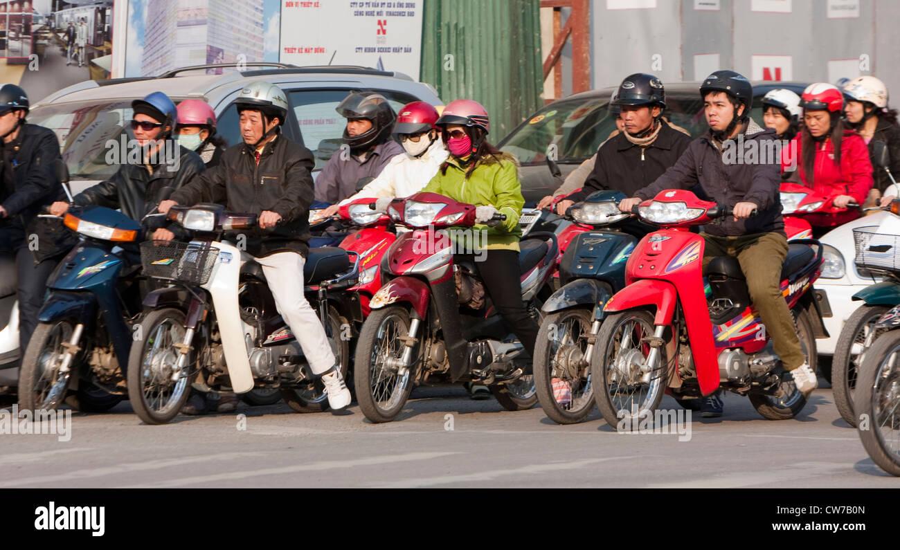 Rangée de motocyclistes en attente à un trafic signe, Vietnam, Hanoi Photo Stock