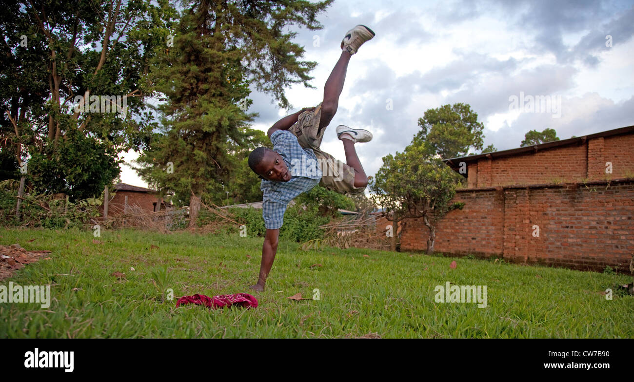 Teenage boy montrant un breakdance figure sur une pelouse faisant un ATR sur un bras, Burundi, Makamba, Makamba Photo Stock