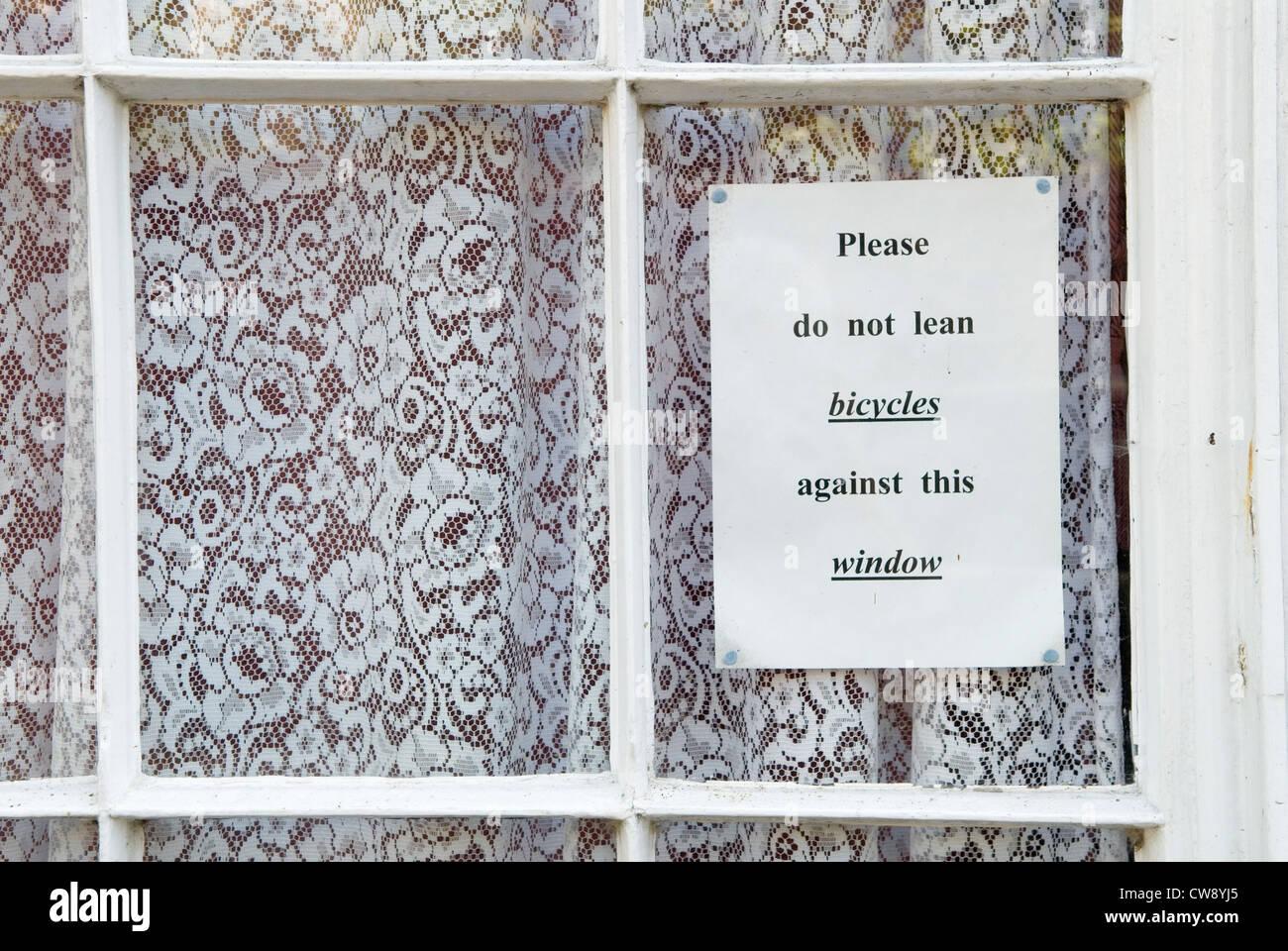 Veuillez ne pas s'appuyer contre des vélos cette fenêtre signer en maison privée dans la rue Photo Stock