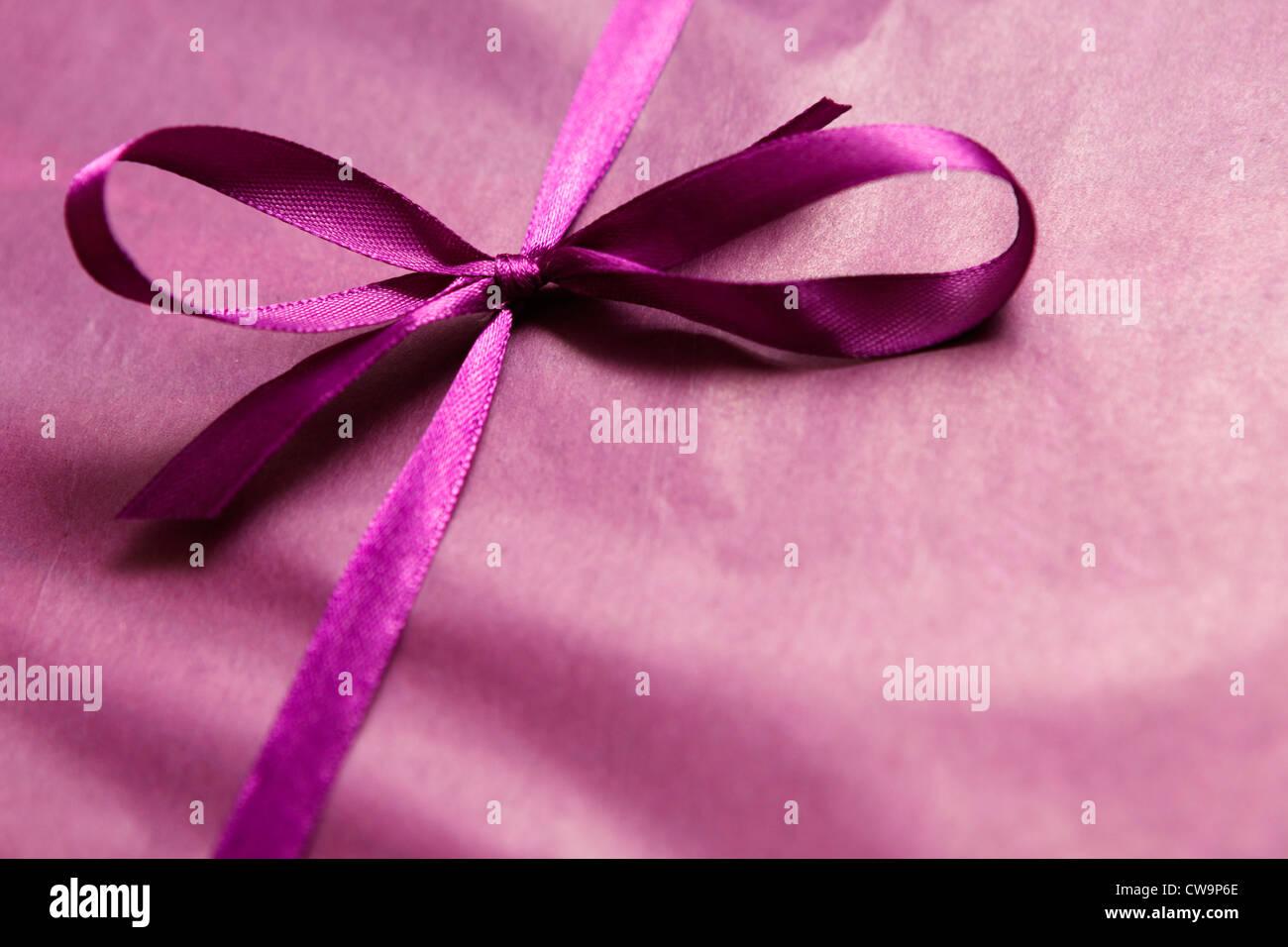 Un cadeau enveloppé dans du papier de soie pourpre et satiné Photo Stock