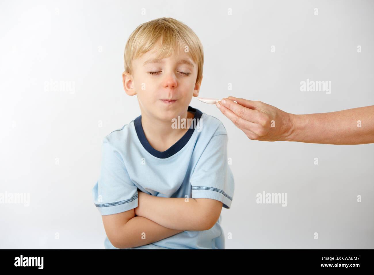 Fils de parents essayant de donner médecine, garçon refusant Photo Stock