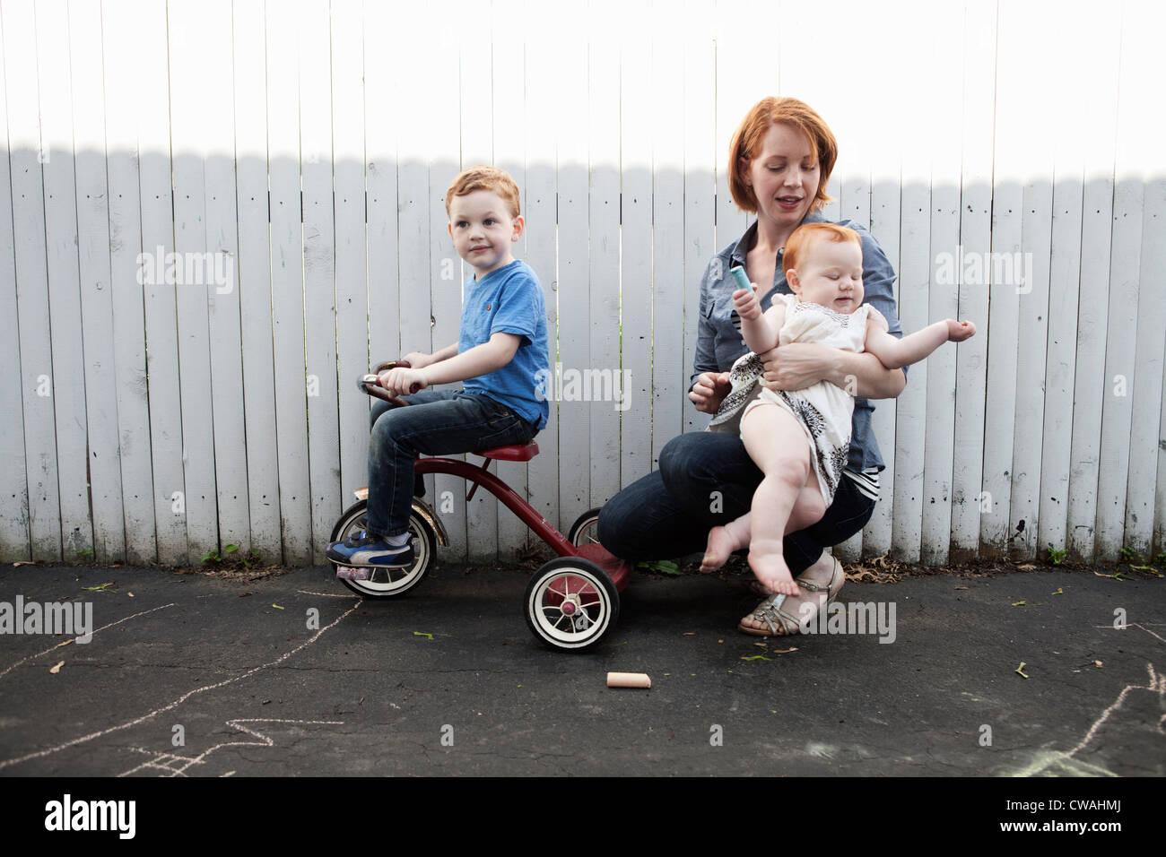 Mère jouant dans cour avec deux enfants Photo Stock