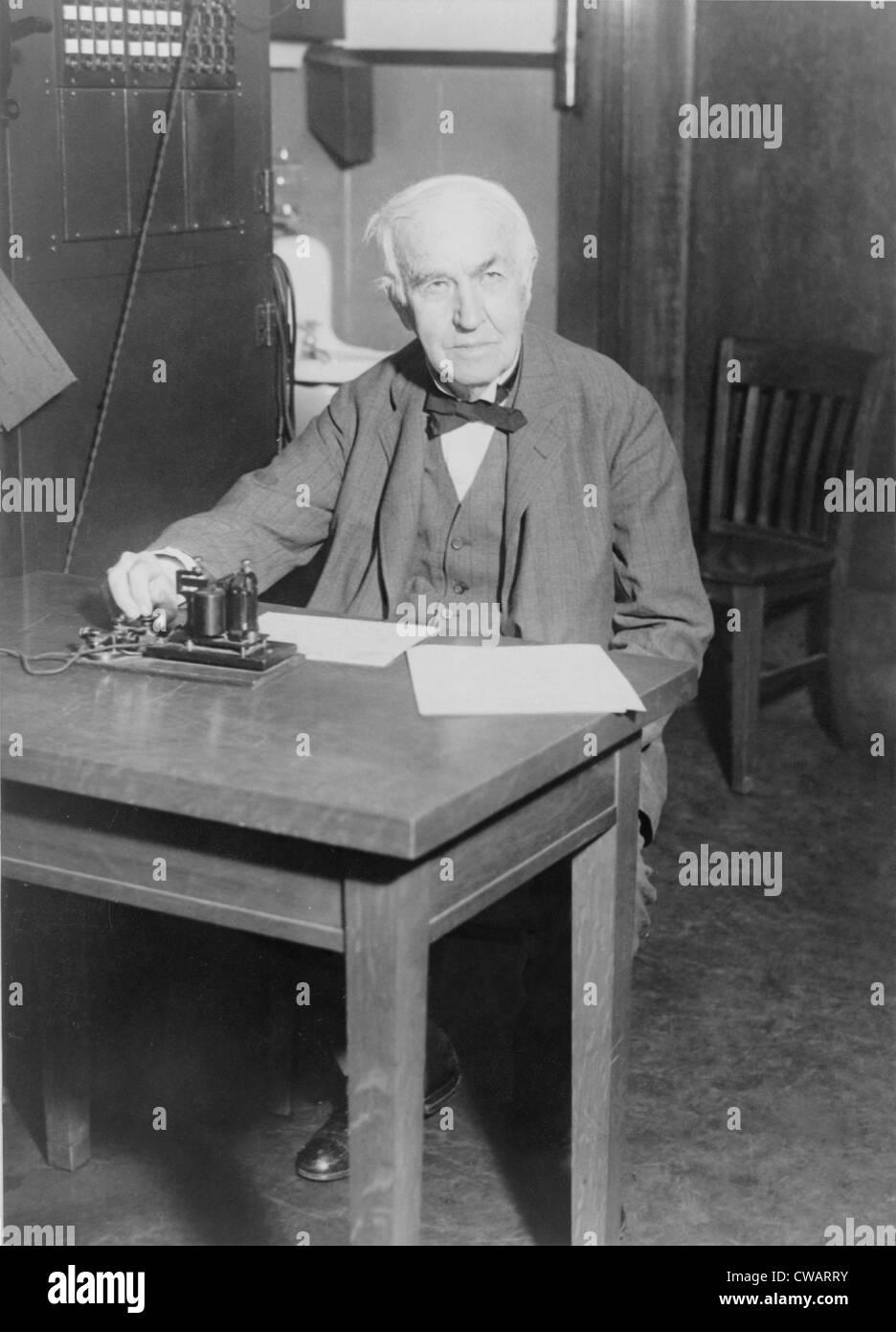 Thomas Edison, assis au bureau, démontrant un vieux télégraphe émetteur à son West Orange, New Jersey, de laboratoire, 1930. Banque D'Images