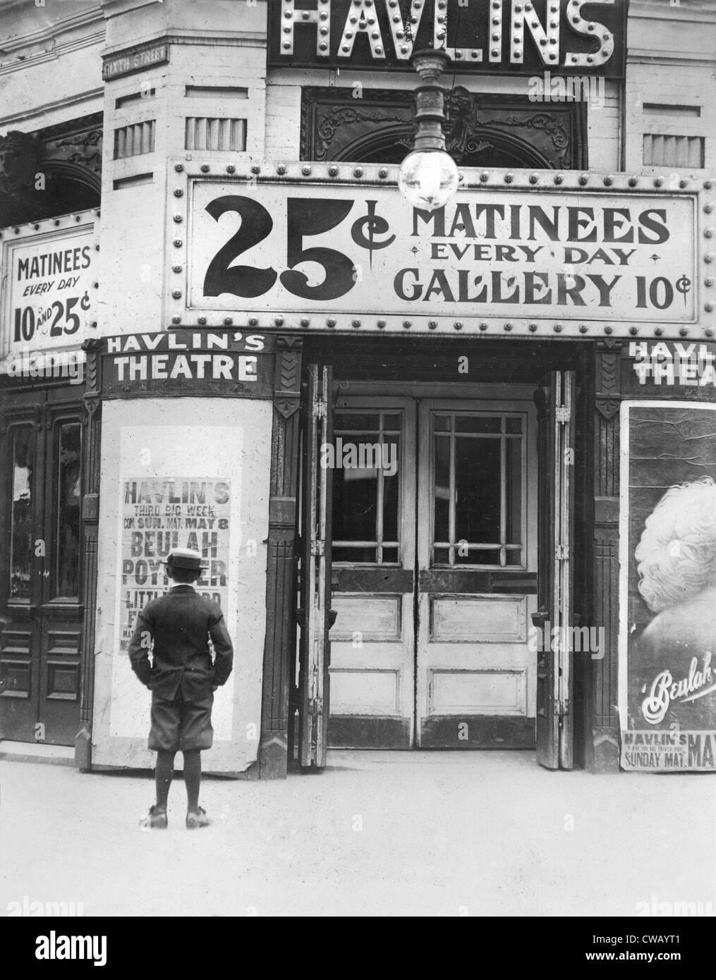 Garçon en face d'un cinéma montrant un film avec Beulah Poynter, légende originale cite: Photo Stock