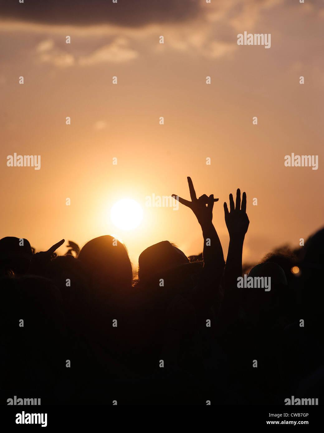 Le soleil se couche sur la foule. 2 mains en silhouette la V (la victoire). V Festival le 19/08/2012 à Hylands Park, Banque D'Images