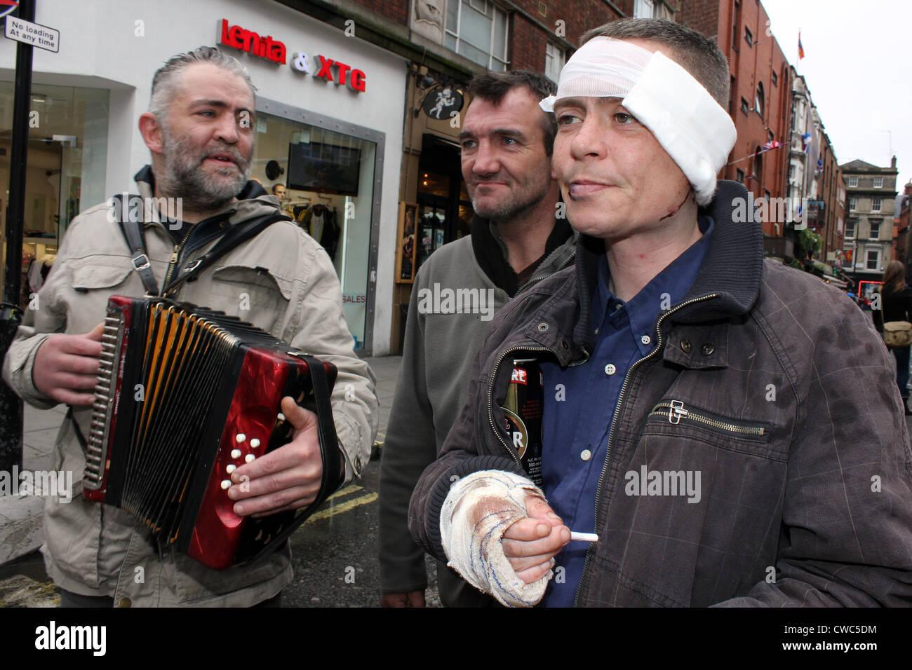 Groupe d'hommes sans abri ensemble en jouant de la musique de rue Photo Stock