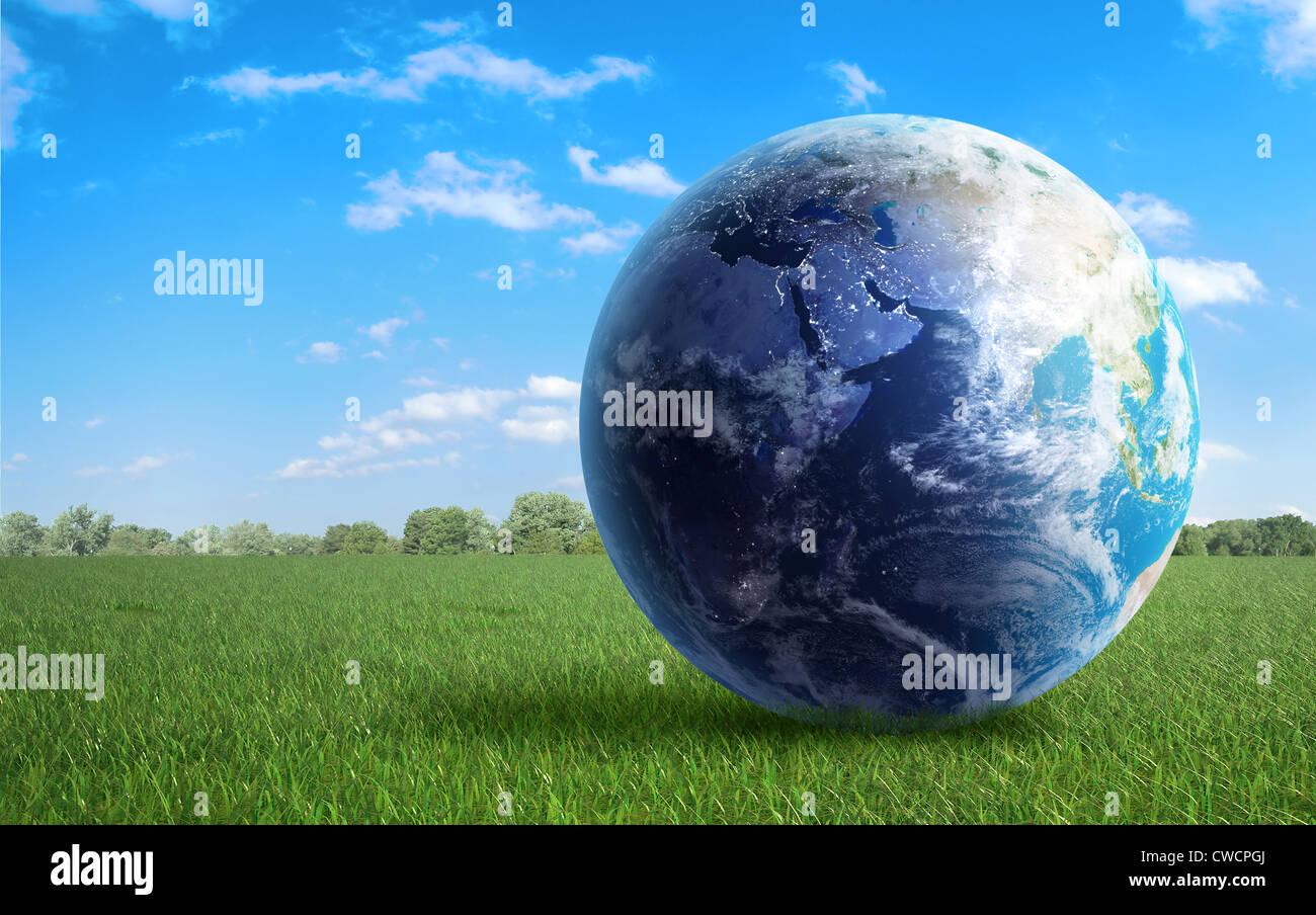 Globe terrestre sur un champ d'herbe verte Photo Stock