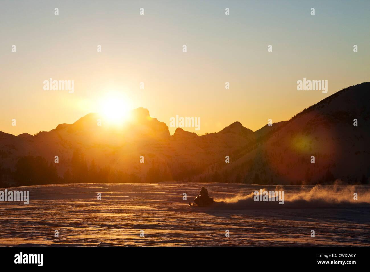 Un jeune homme athlétique de la motoneige au coucher du soleil, dans le Montana. Photo Stock