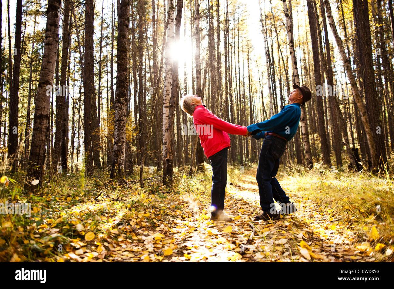Un heureux couple de retraités rire et sourire alors que l'occasion d'une randonnée à travers une forêt pendant Banque D'Images