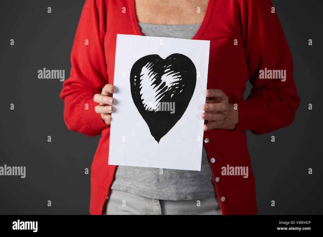 Senior woman holding dessin à l'encre du coeur Photo Stock