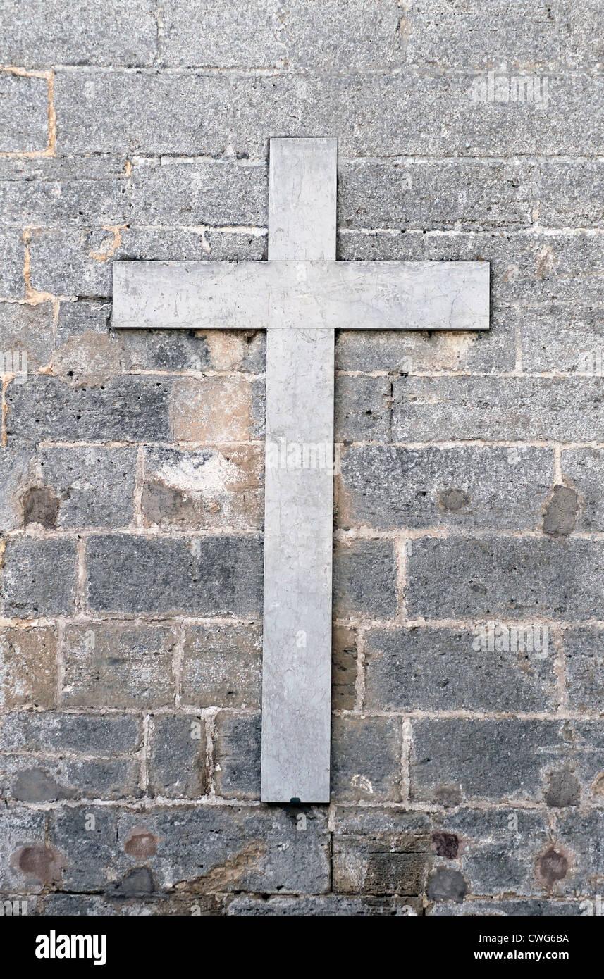 Ancienne croix religieuse en marbre gris ou gris sur le mur. Photo Stock