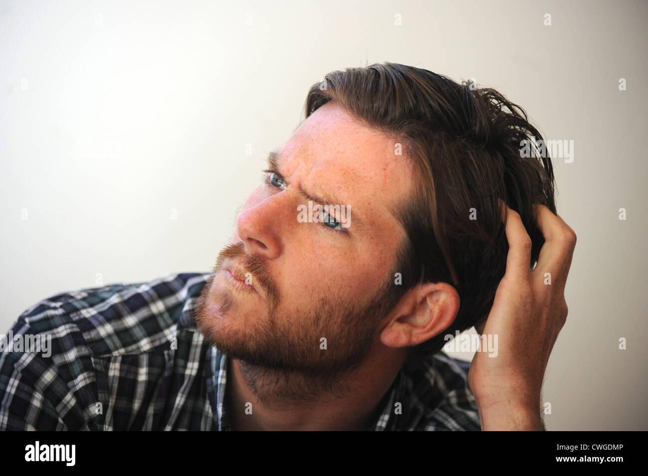 Jeune homme la pensée de travail intense expressive scratching head mad Photo Stock