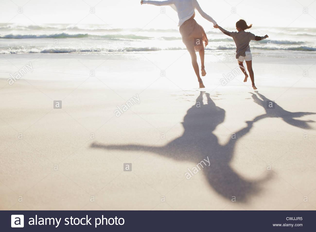 Mère et fille se tenant la main et s'exécutant sur sunny beach Photo Stock